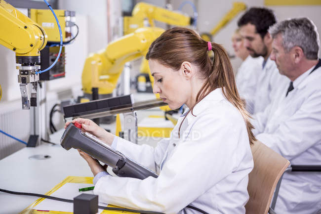Engineers examining industrial robots — Stock Photo