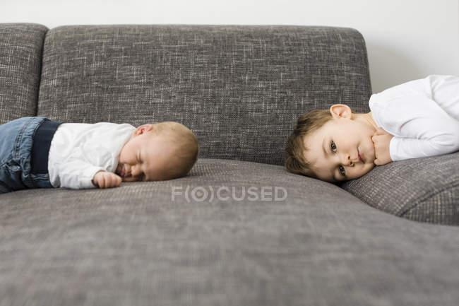 Спящая новорожденного мальчика и его брат на диване — стоковое фото