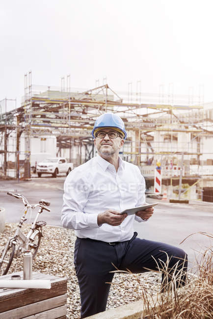 Man with tablet at construction site — Stock Photo