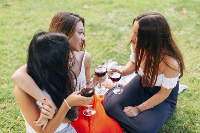 Amici che tengono bicchieri di vino rosso — Foto stock