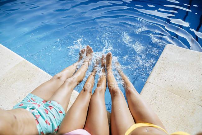 Gambe di amici spruzzi in piscina — Foto stock