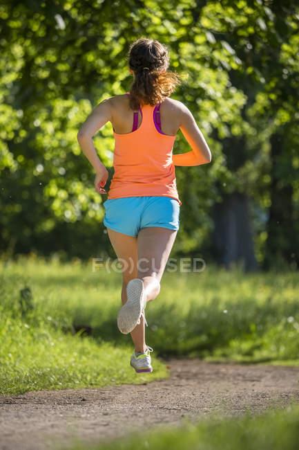Молода жінка біжить в парку. — стокове фото