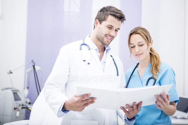 Deux médecins souriants, tenue de dossier — Photo de stock
