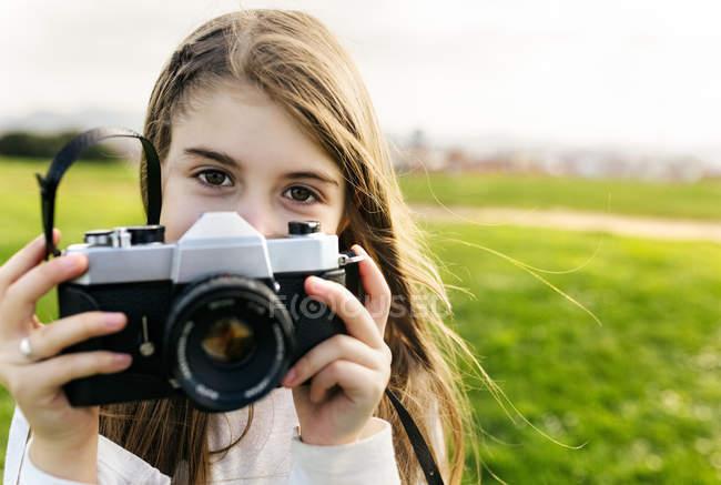 Girl holding an retro camera — Stock Photo