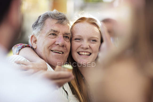 Granddaughter hugging grandfather outdoors — Stock Photo