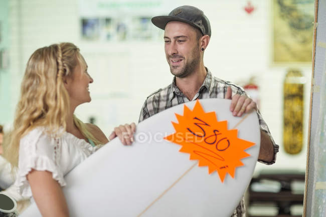 Shop assistant showing surfboard prices — Stock Photo