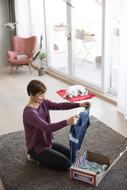 Pacco disimballaggio donna con indumento — Foto stock