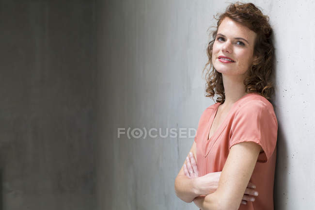 Woman leaning against concrete wall — Stock Photo