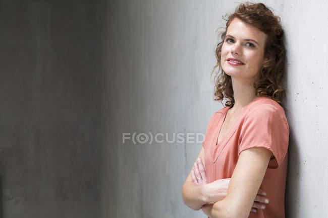 Женщина прислонилась к бетонной стене — стоковое фото