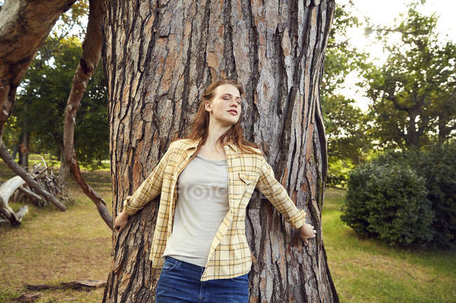 Woman leaning against tree trunk — Stock Photo