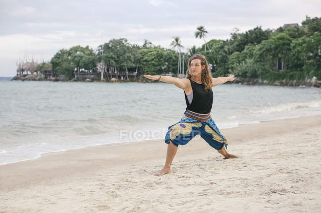 Donna che pratica Yoga sulla spiaggia — Foto stock