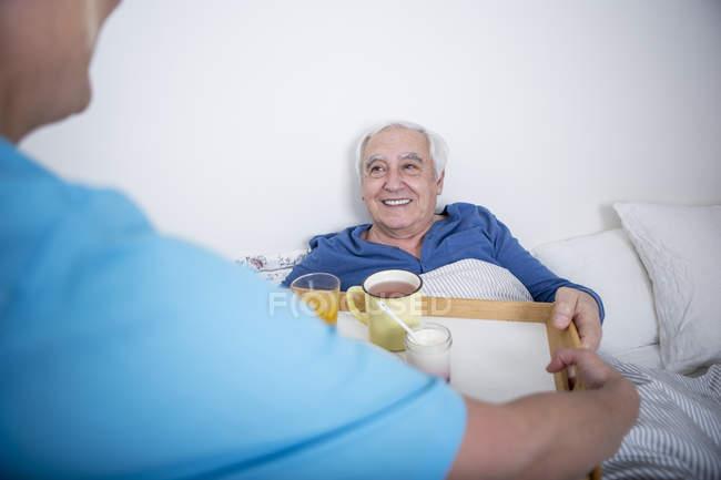 Krankenschwester bringt Tee am Patientenbett — Stockfoto