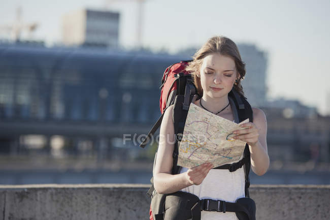 Germany, Berlin, Young woman with backpack looking at map — Stock Photo