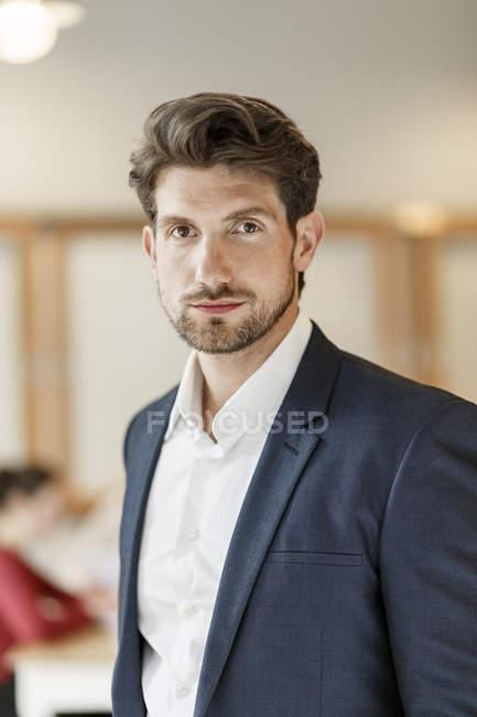 Бизнесмен в кабинете, глядя на камеру — стоковое фото