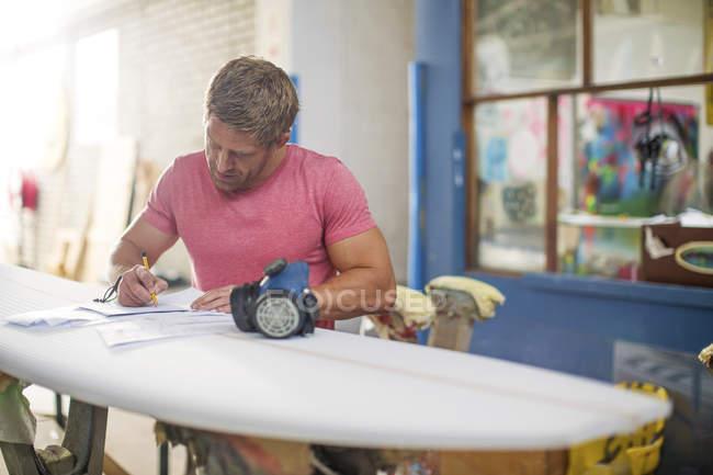 Surfshop-Mitarbeiter füllt Papierkram aus — Stockfoto