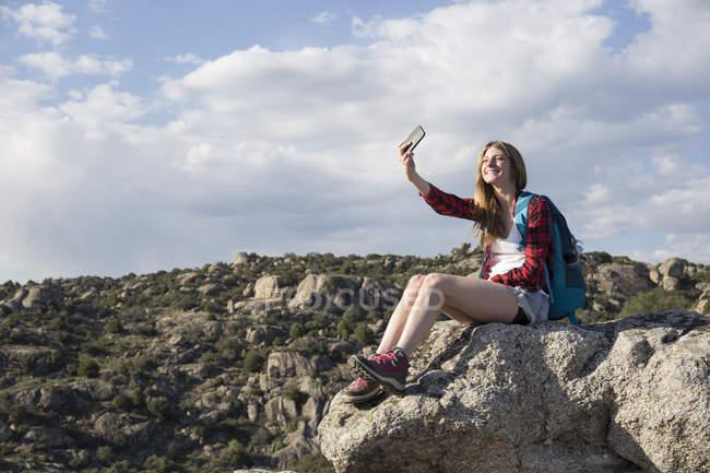 Femme prenant selfie tout en se reposant sur la roche — Photo de stock