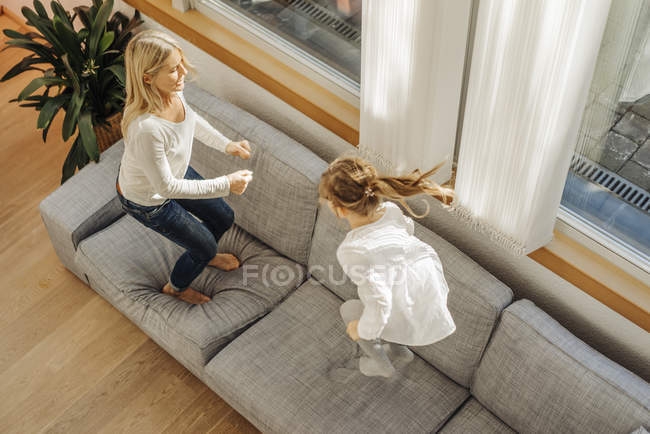 Woman and girl bouncing on couch — Stock Photo