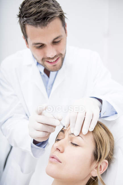 Woman receiving injection into forehead — Stock Photo