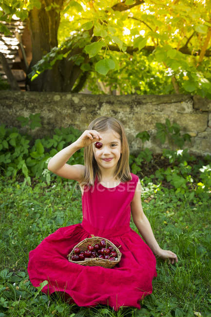 Дівчинка сидить на луг з кошиком вишні — стокове фото