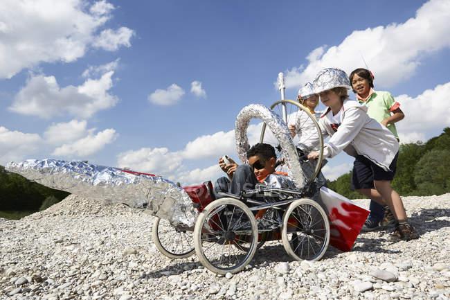 Quatre garçons avec fusée auto-fabriquée jouant à l'atterrissage sur la lune — Photo de stock
