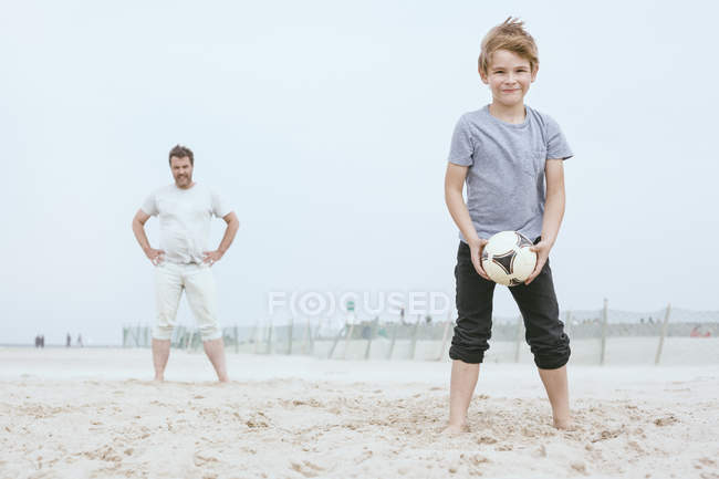 Portrait of smiling little boy playing with father on the beach — Stock Photo