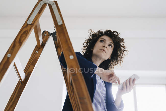 Businesswoman standing by ladder — Stock Photo