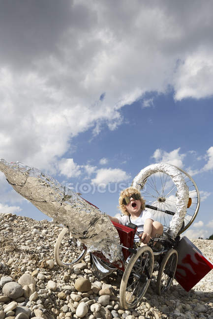 Boy sitting in a self made rocket — Stock Photo