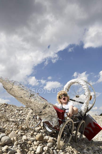 Niño sentado en un cohete auto-hecho - foto de stock