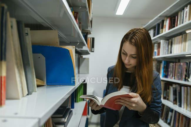 Livre de lecture étudiant à la bibliothèque — Photo de stock