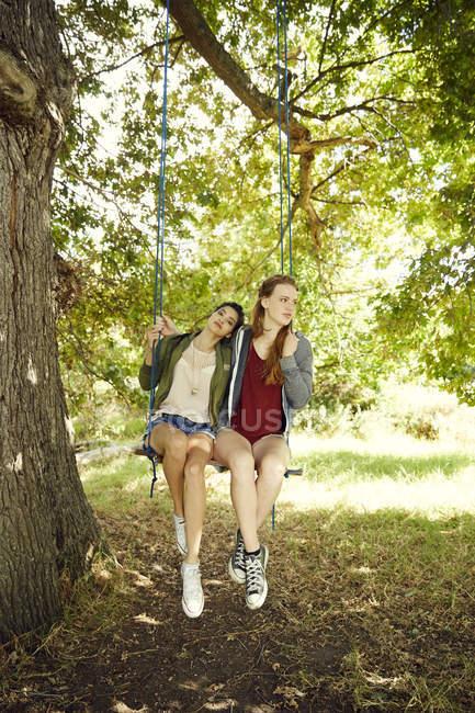Freunde sitzen zusammen auf Schaukel — Stockfoto
