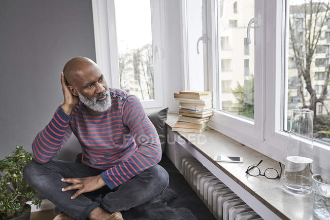 Hombre sentado con las piernas cruzadas en la ventana - foto de stock