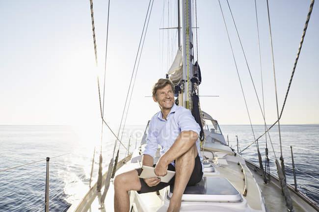 Человек с цифровым планшетом на парусной лодке — стоковое фото
