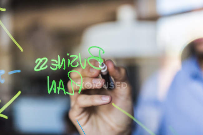Businessman writing on glass wall — Stock Photo