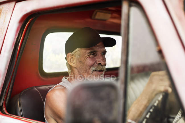 Senior man driving an old pick up — Stock Photo