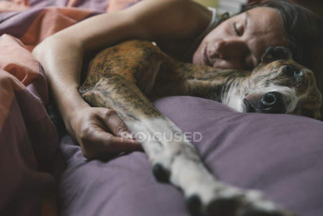 Mulher deitada na cama com seu cachorro — Fotografia de Stock