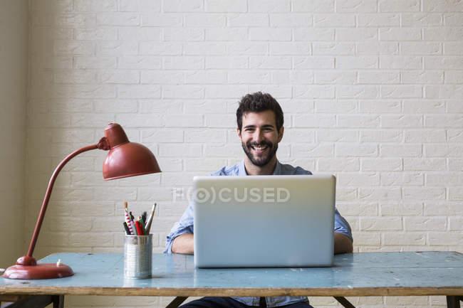 Homem sentado na mesa trabalhando com laptop — Fotografia de Stock