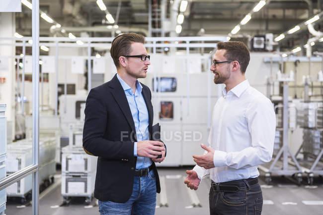 Men interacting in shop floor — Stock Photo