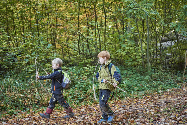 Two boys walking through forest with bows and arrows — Stock Photo