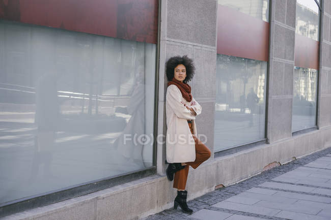 Woman leaning on shop building — Stock Photo