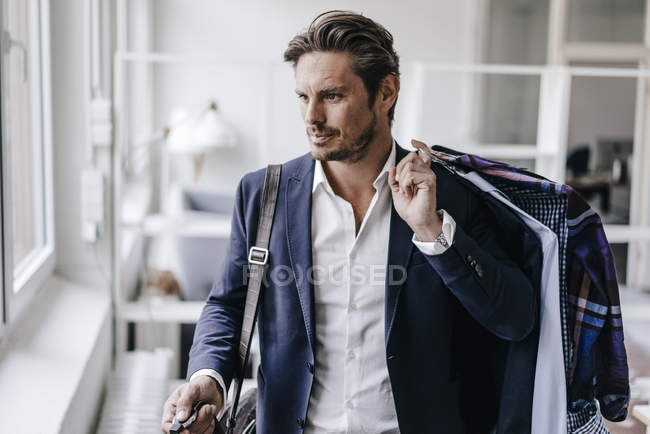 Businessman carrying clothes on hangers — Stock Photo
