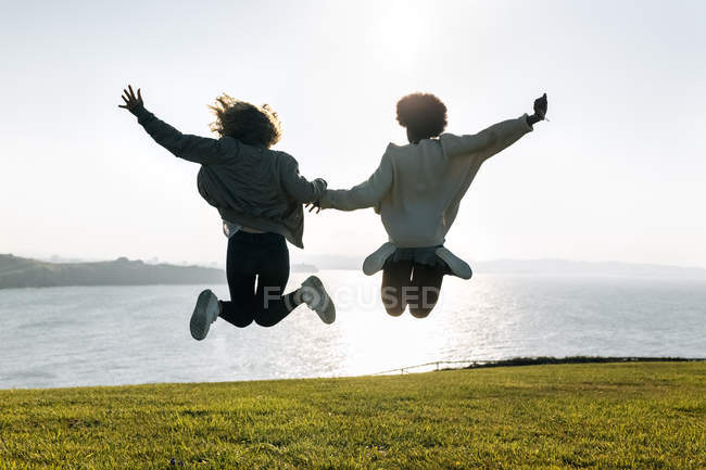 Best friends jumping on coast — Stock Photo