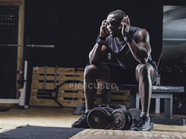 Atleta sentado en el gimnasio - foto de stock