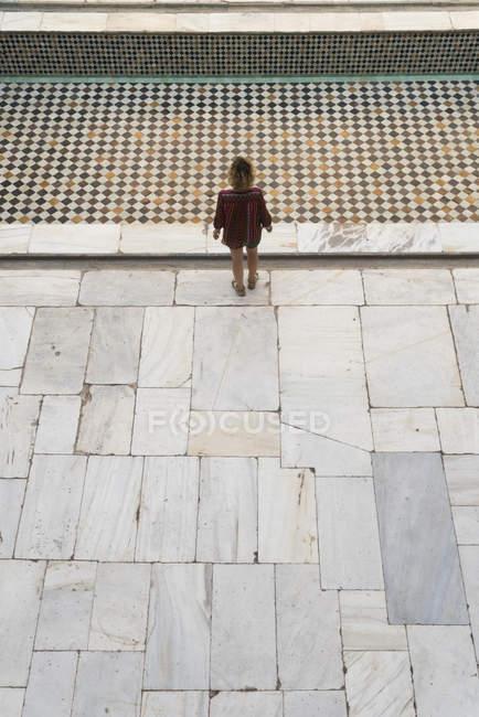 Женщина стоит на кафельном полу — стоковое фото
