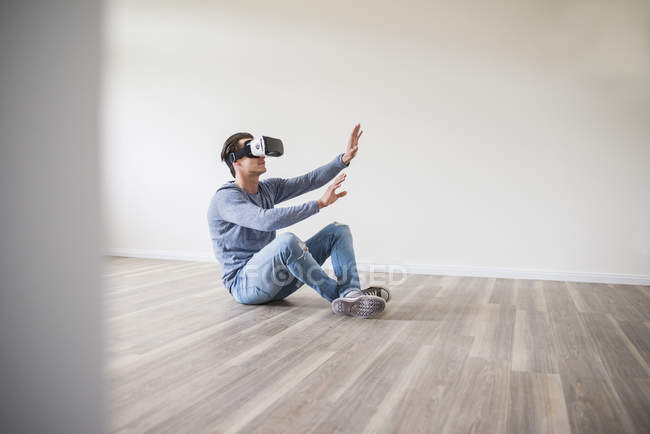 Man in empty apartment wearing virtual reality glasses — Stock Photo