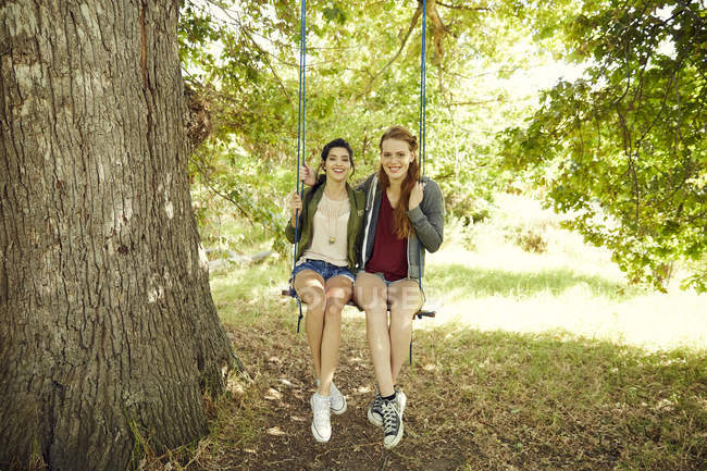 Friends sitting together on swing — Stock Photo