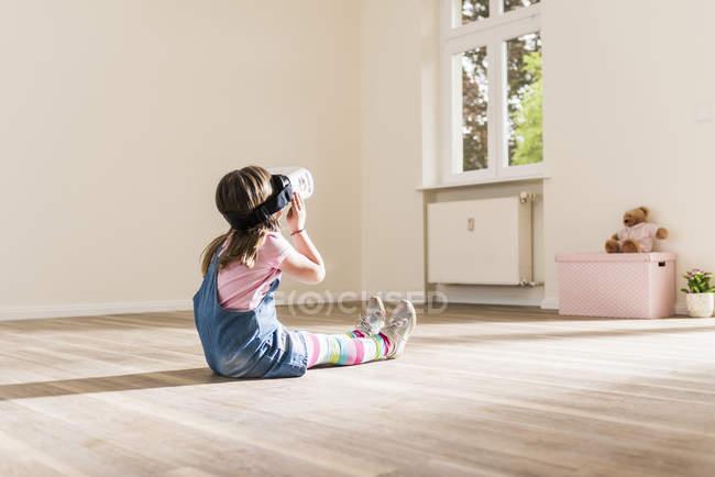 Chica en apartamento vacío con gafas de realidad virtual - foto de stock
