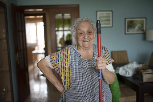 Senior woman holding cleaning mop — Stock Photo