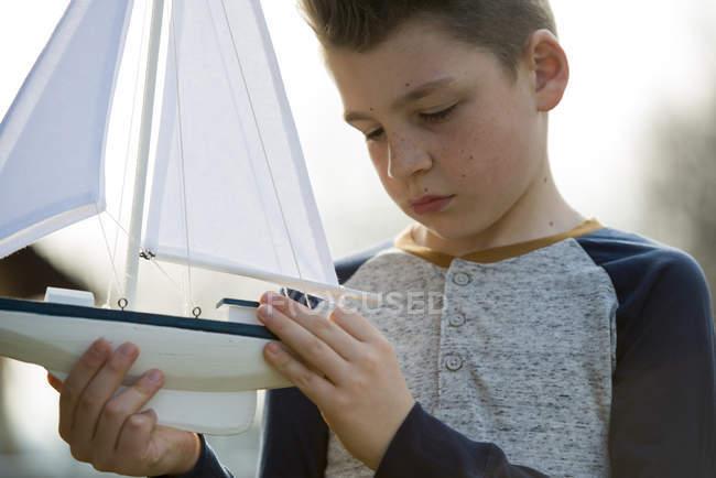 Хлопчик грає з іграшкою човен — стокове фото