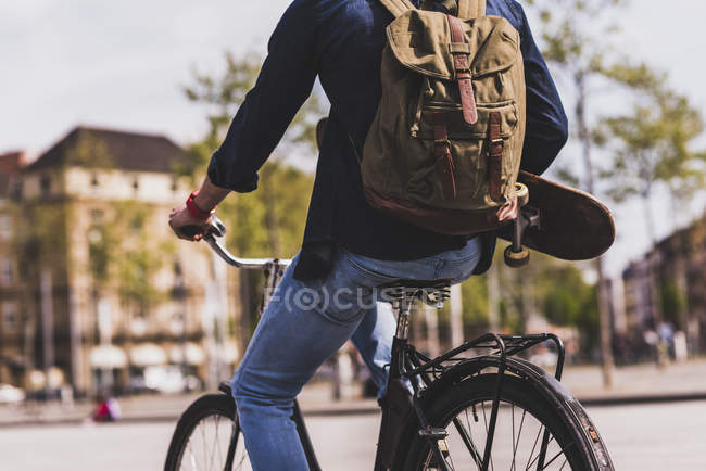Man holding skateboard while riding bicycle — Stock Photo