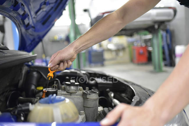 Car mechanic checking motor oil — Stock Photo